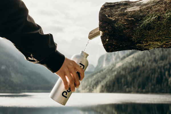 Hand holding a water bottle under a water spout in a tree trunk